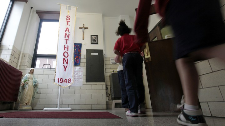 Students at a Catholic school pass a statue of the Virgin Mary and a crucifix on their way to class.