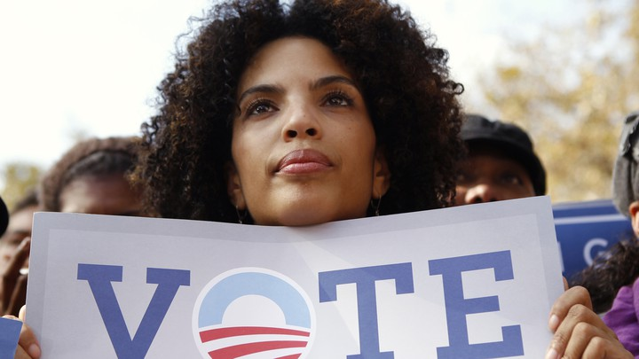 "A woman holding a ""Vote"" sign with the Obama campaign logo as the ""o"""