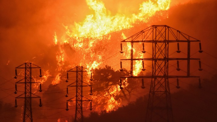 In this December 16, 2017, file photo provided by the Santa Barbara County Fire Department, flames burn near power lines in Sycamore Canyon near West Mountain Drive in Montecito, California.