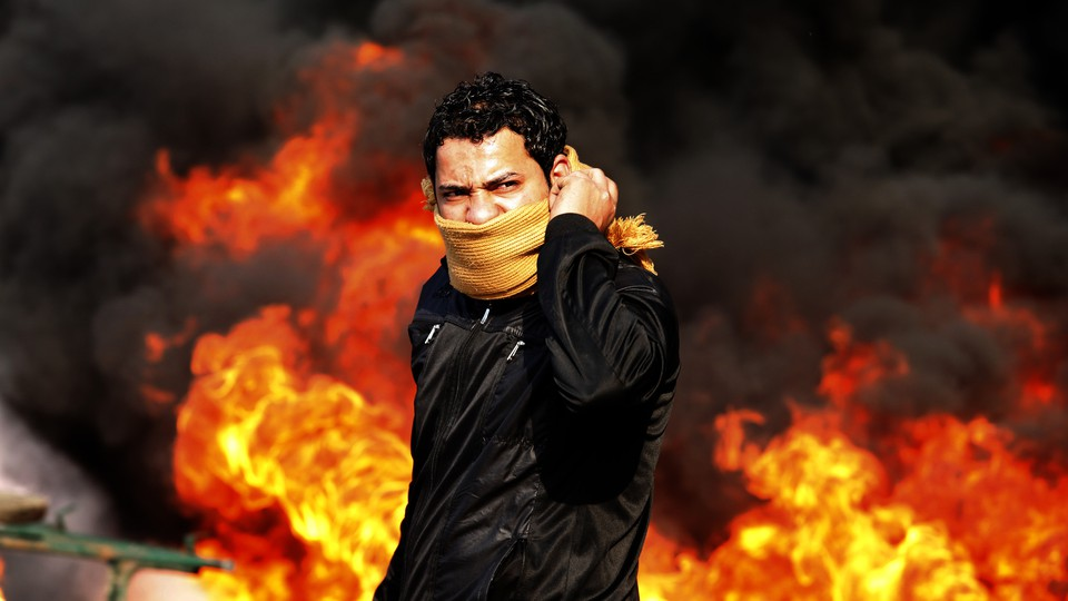 A protestor against the backdrop of a burning flame.