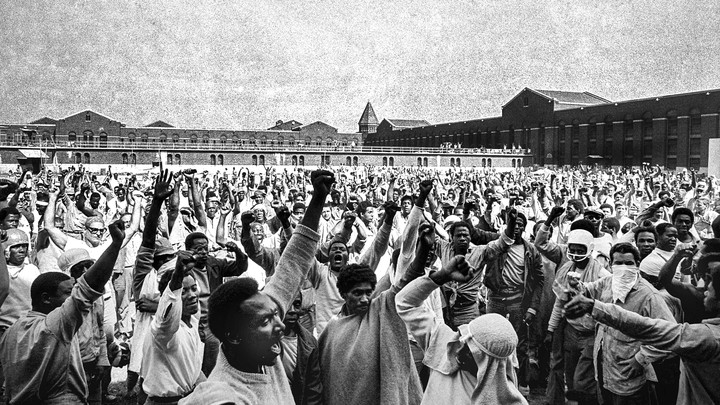 """A black and white photograph depicts hundreds of inmates in the interior yard of Attica prison. Many have their hands raised in the """"Black Power"""" gesture."""