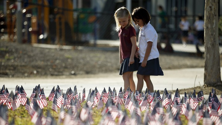 Two girls walk through a field filled with American flags.