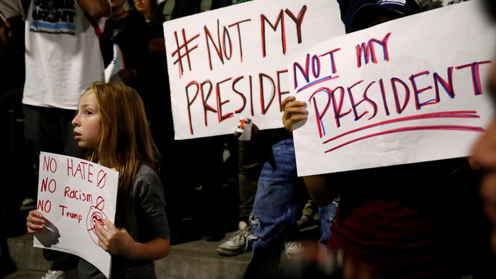 """Protesters, including a young girl, hold signs reading """"not my president"""" and """"no hate, no racism, no Trump."""""""