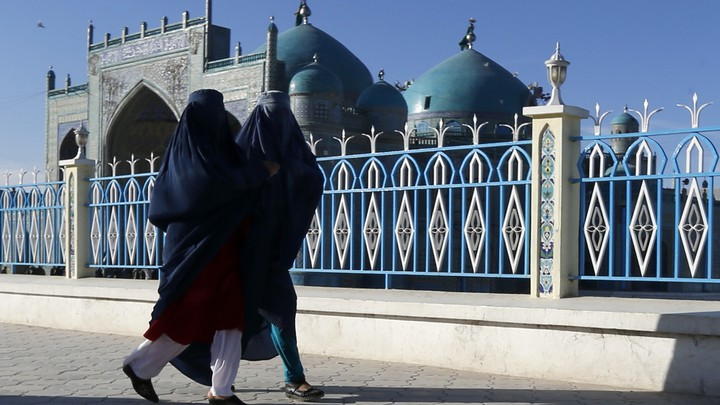 Two women walk past a mosque in Afghanistan