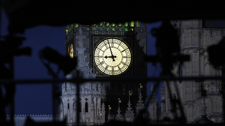 An illuminated clock on the face of Big Ben shines brightly against a dark sky.