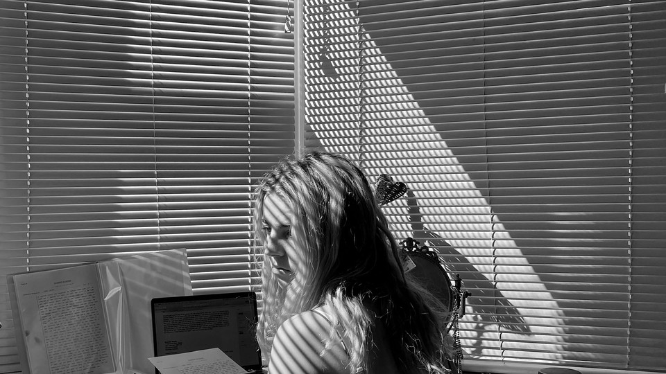 A woman sits at her desk unhappily
