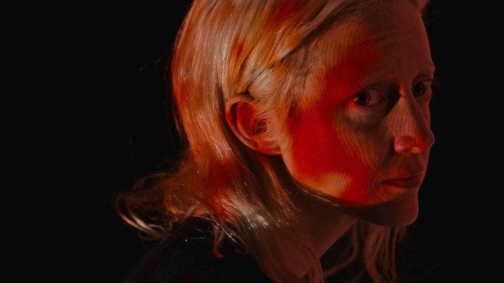 A close-up of a woman with splotchy red light on her face