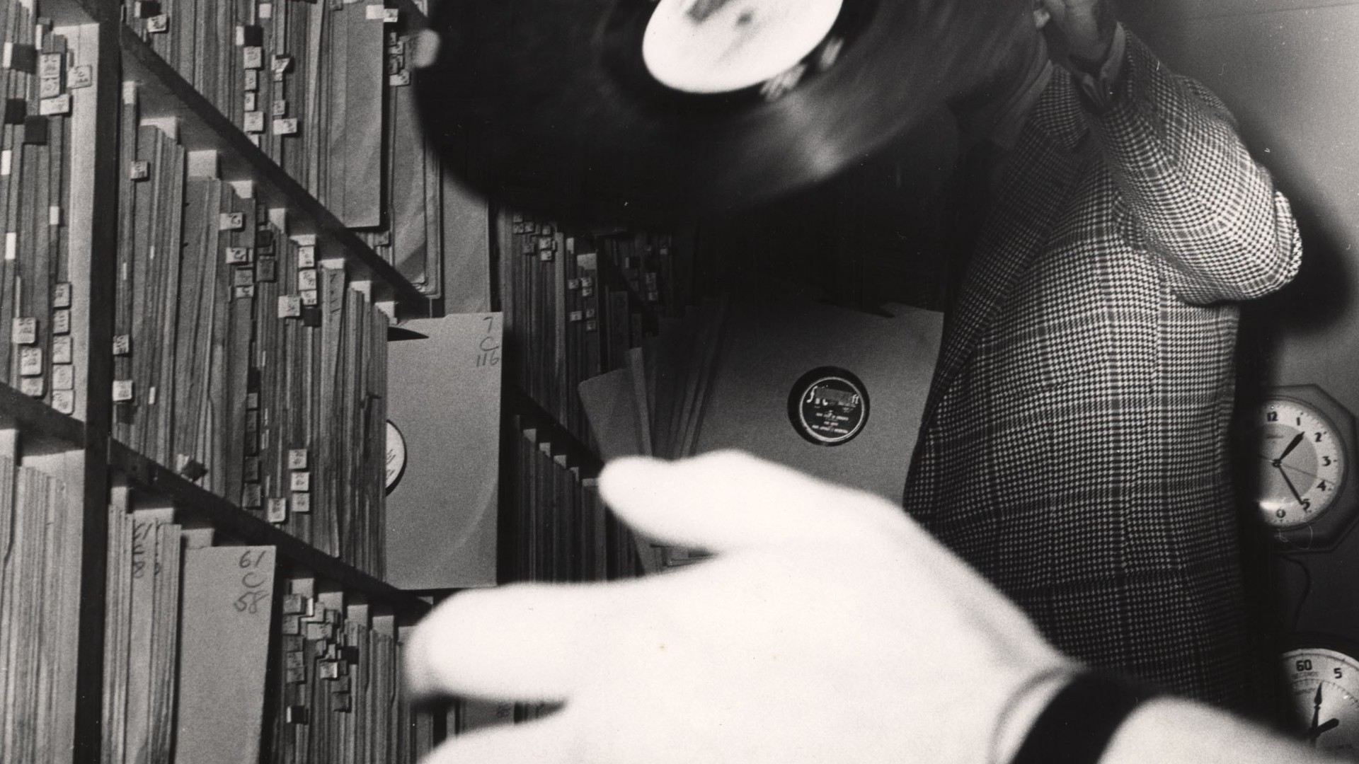 A black-and-white photo of a man in a plaid suit holding up a record, his face obscured