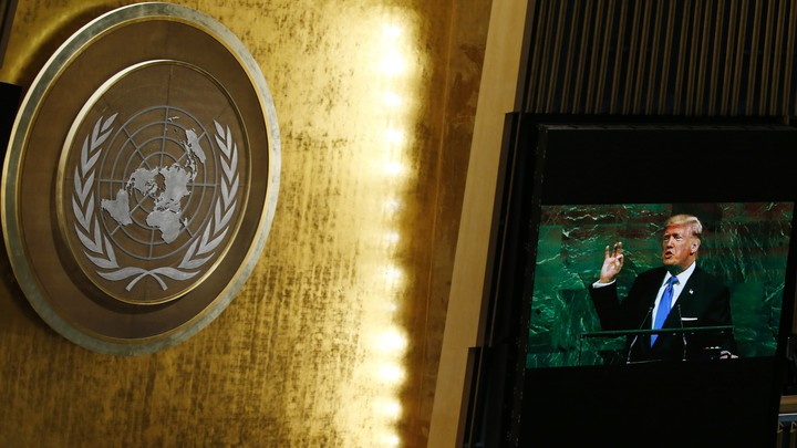 President Trump appears on a screen opposite the United Nations logo