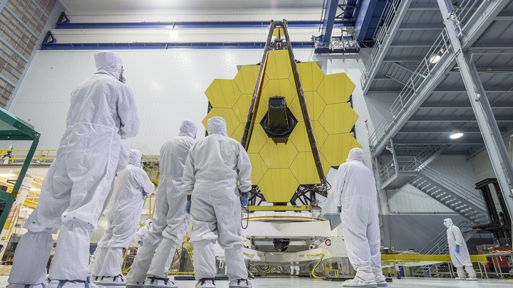 NASA employees, dressed in white uniforms, look up at the gold-plated mirrors of the James Webb Space Telescope.