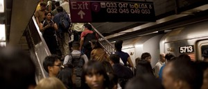A crowd mills around a subway platform and up the stairs at a New York City subway station