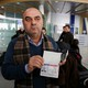Fuad Sharef Suleman shows his USA visa to the media after returning to Iraq from Egypt.