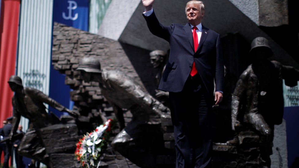 U.S. President Donald Trump waves on stage in front of a national monument before his speech in Warsaw, Poland