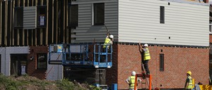 Construction workers build affordable housing units.