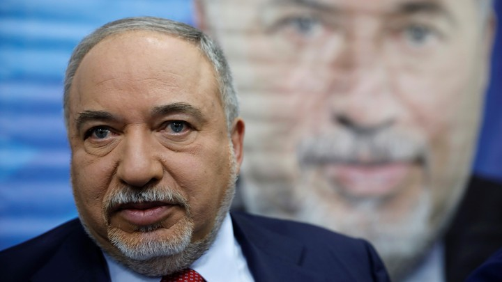 Avigdor Lieberman stands in front of a painted image of himself.