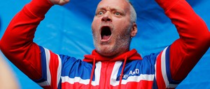 A man in an Icelandic-flag shirt cheers and raises his arms at a soccer match.