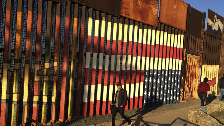 People walk past a mural painted on a border structure in Tijuana, Mexico.