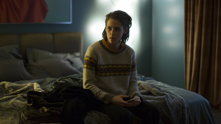 Kristen Stewart sitting on a bed with her phone in 'Personal Shopper'