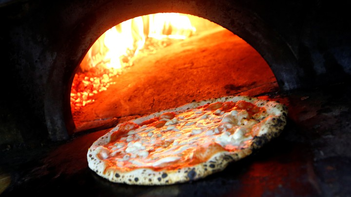A pizza in front of an open brick oven