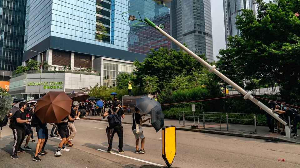 Protesters in Hong Kong take down a lamppost
