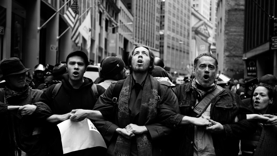 Occupy Wall Street protesters stand in a row with their arms linked