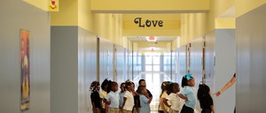 Young children line up in the hallway outside a classroom in an elementary school.