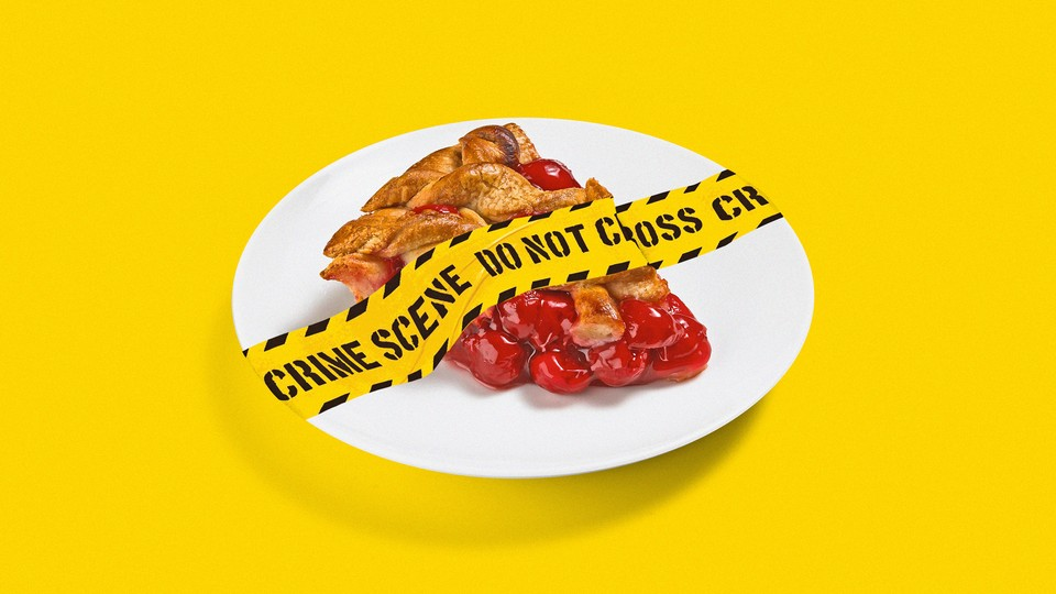 Police tape stretched across a piece of pie on a plate