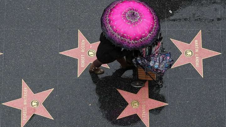 An umbrella seller walks on the Hollywood Walk of Fame in the rain in Hollywood, Los Angeles