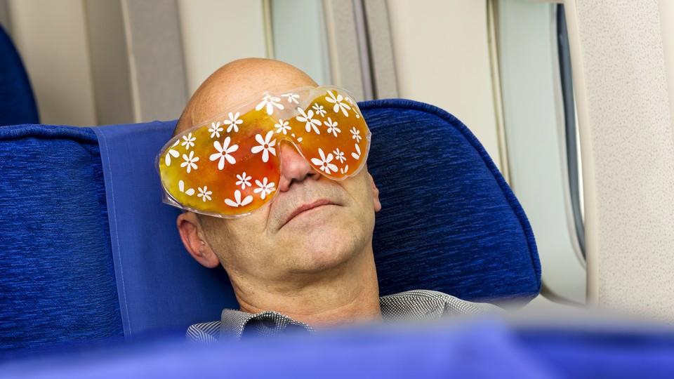 A man asleep on an airplane