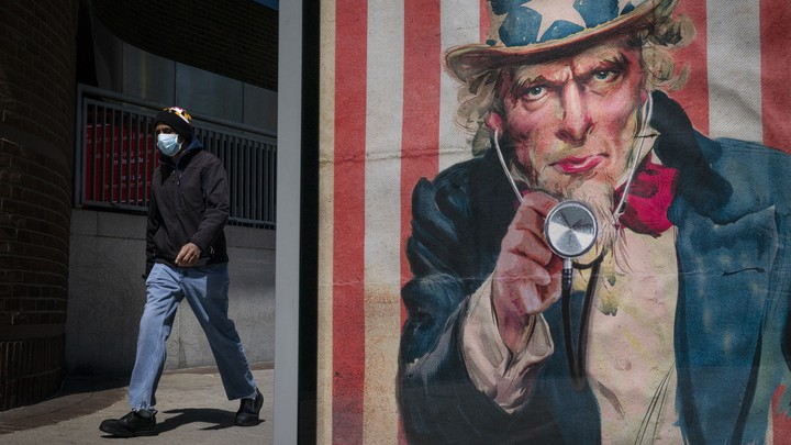 A man in a face mask walks past a bus stop in Washington, D.C.