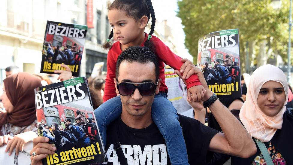 People take part in a demonstration to protest against the mayor of the French city of Beziers and to support Syrian refugees.