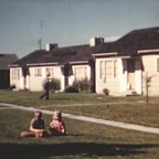 A still from a 1940s film shows two children sitting in front of ranch-style houses.