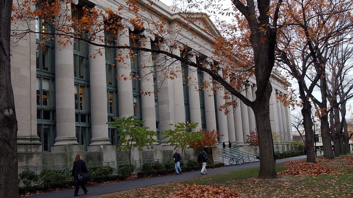 Students walk in front of a large, judicial-looking building on Harvard's Law School campus in the fall.