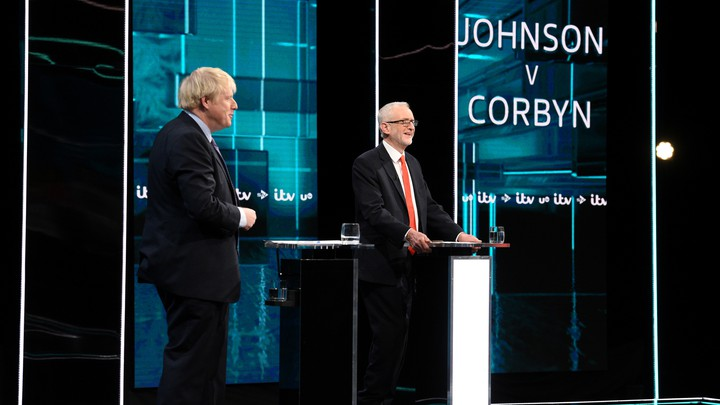 Boris Johnson and Jeremy Corbyn stand in front of lecterns during a TV debate.