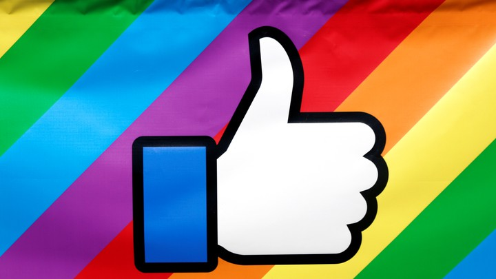 The Facebook thumbs-up logo is displayed on a rainbow-colored banner during the annual Pride parade in New York City, in 2016.