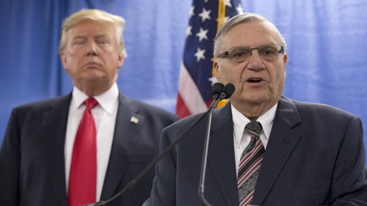 Joe Arpaio speaks with President Trump behind him.