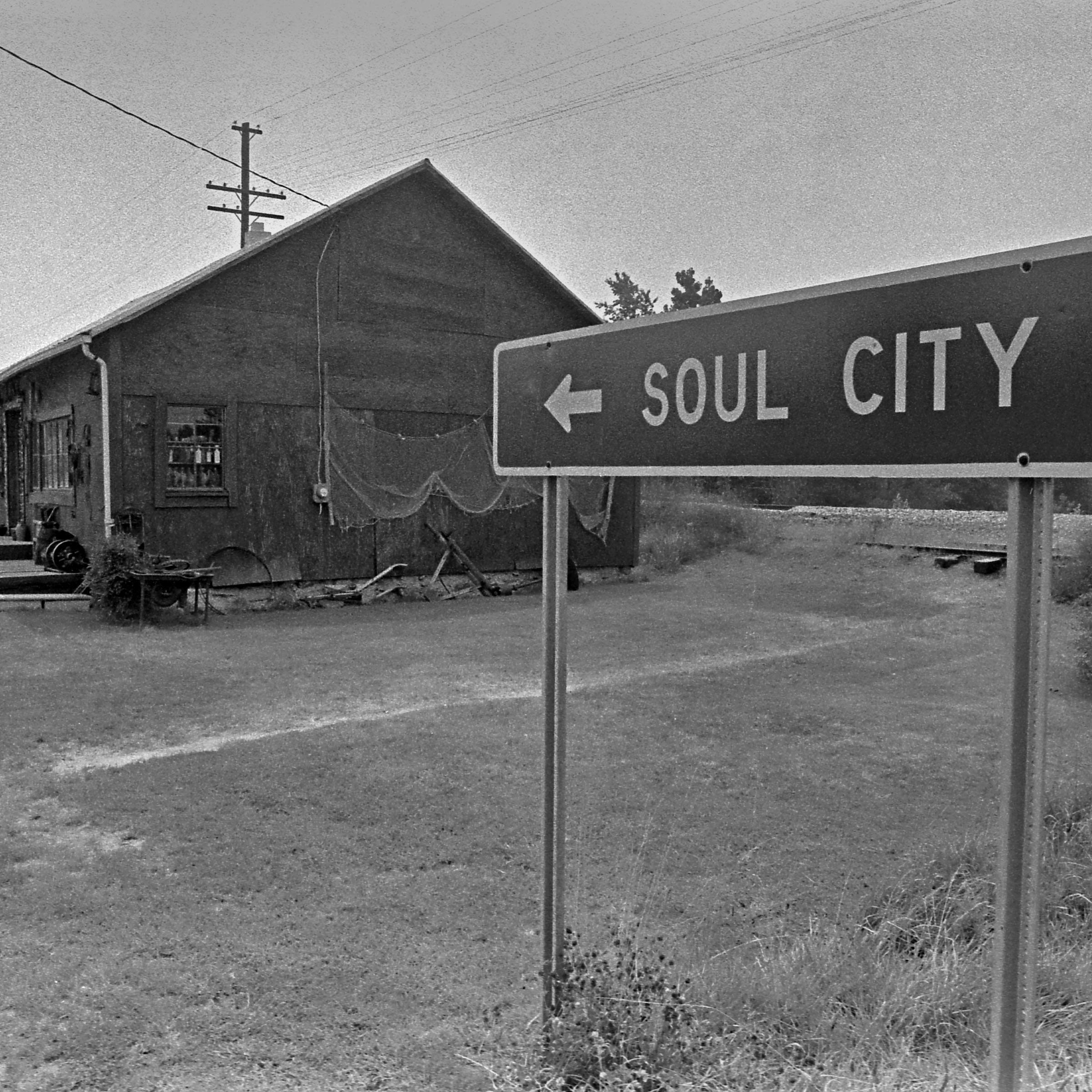 A black and white photo of a sign pointing to Soul City