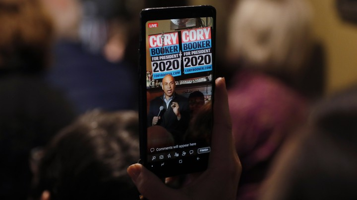 Cory Booker, seen through a cellphone, speaking in Marshalltown, Iowa