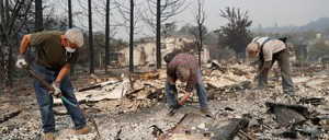 A group of retired police officers works through the ruins of the Tubbs Fire in Santa Rosa, California.