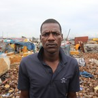 A man in a polo shirt stands in a large garbage dump.
