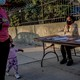 A woman and child walk past a voter-registration table in Brooklyn. Another woman is sitting at the table. Both adults are wearing masks.