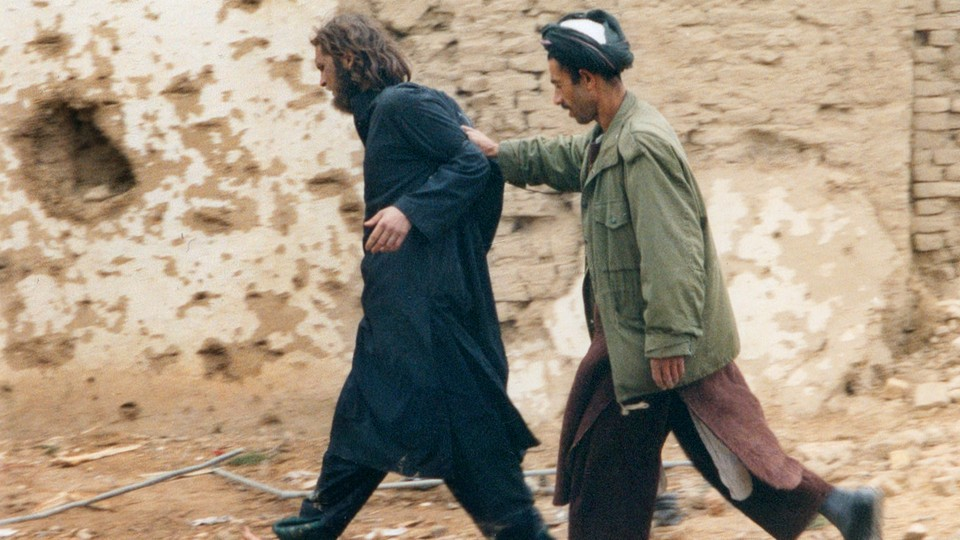 John Walker Lindh is escorted by a Northern Alliance fighter after his capture in Afghanistan in December 2001.