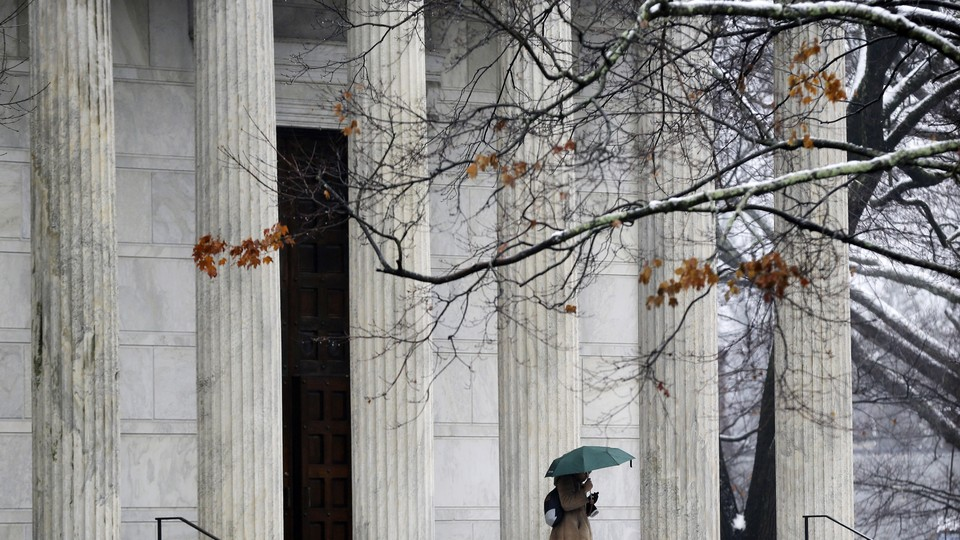 A person with an umbrella walks outside on the Princeton University campus.