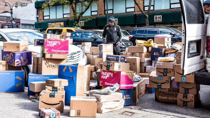 A deliveryman stands in a sea of subscription-service boxes on a sidewalk in NYC.