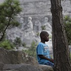 A boy sits in front of Stone Mountain—the Atlanta-area monument to the Confederacy.