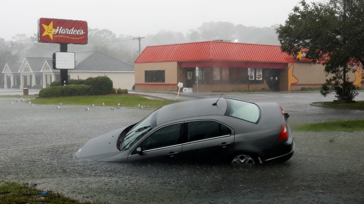 A car washed away by flood waters remains partially submerged in the torrential rains that followed Hurricane Florence.