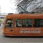 South Lake Union streetcar with an advertisement for Amazon passes by an Amazon office building.