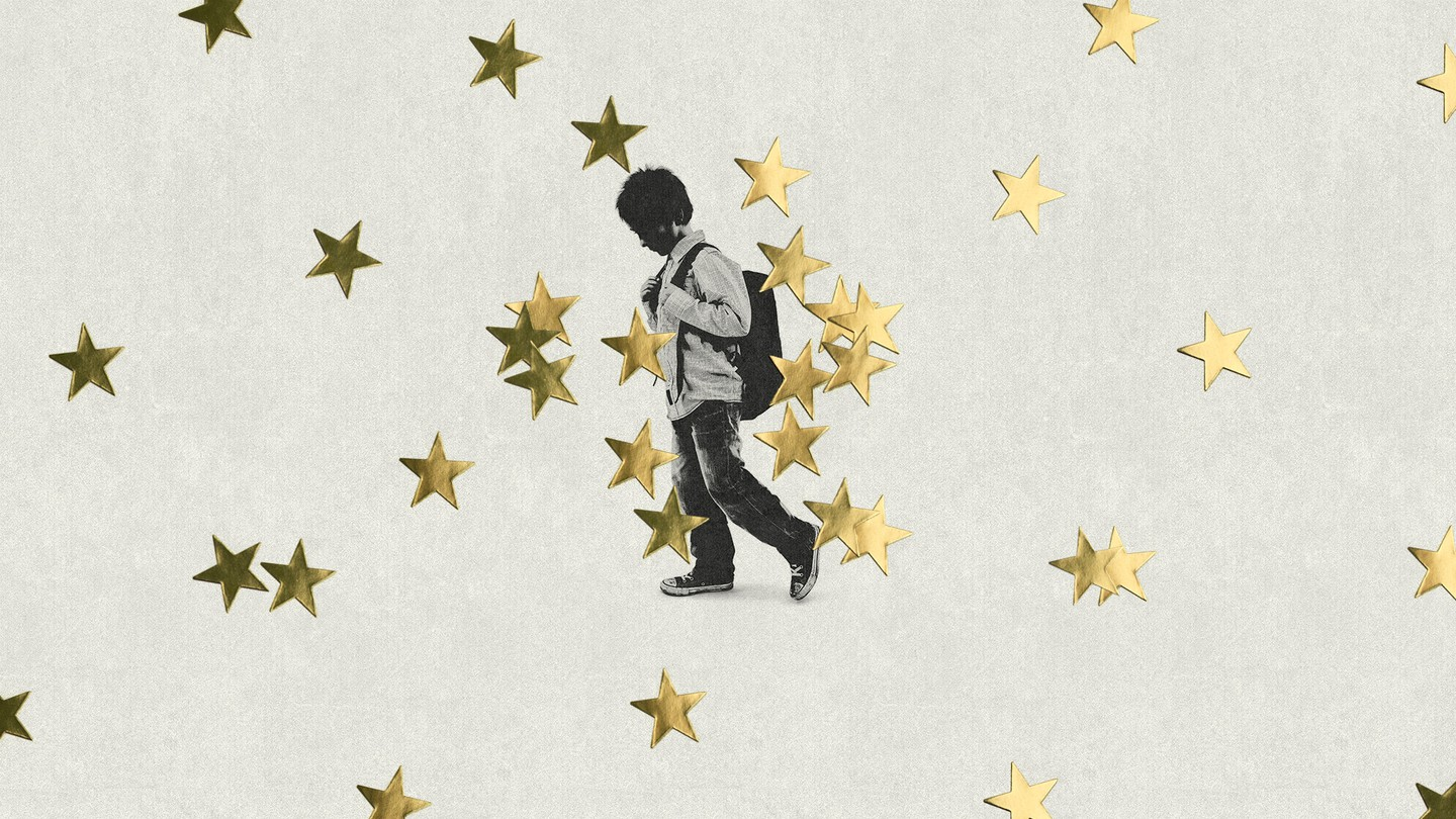 Young boy drags his foot in front of background of gold stars