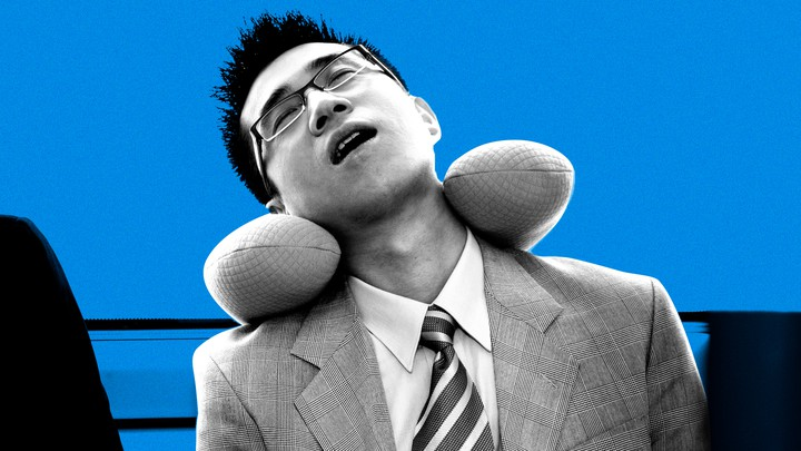 A businessman asleep on public transport using a neck pillow