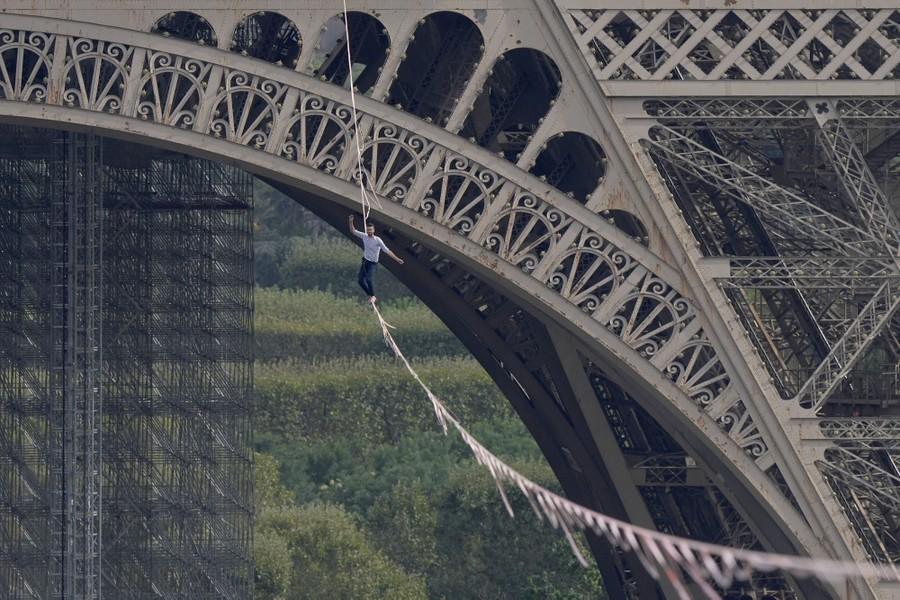 A man walks a slackline attached to the Eiffel tower